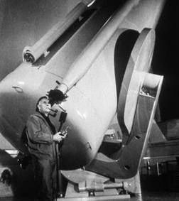 Edwin Hubble langs zijn gigantische telescoop.
